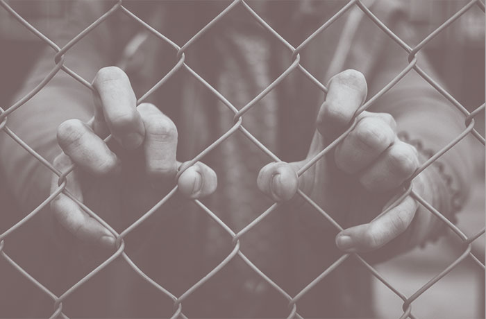 Hands holding fence